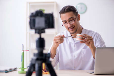 Photo for Young male doctor dentist recording video for his blog - Royalty Free Image