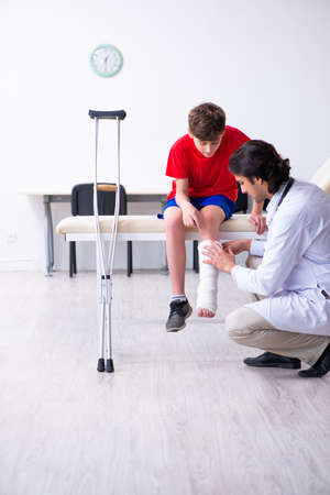 Photo pour Leg injured boy visiting young doctor traumatologist - image libre de droit