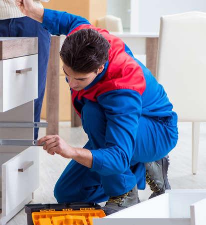 Photo pour The contractor repairman assembling furniture under woman supervisio - image libre de droit