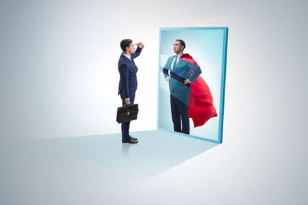 Foto de Businessman seeing himself in mirror as superhero - Imagen libre de derechos