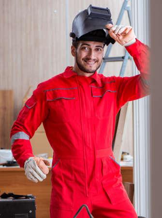 Photo pour Young repairman with a welding gun electrode and a helmet weldin - image libre de droit