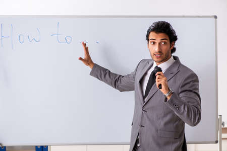 Photo for Young handsome businessman in front of whiteboard - Royalty Free Image