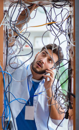 Photo pour Electrician trying to untangle wires in repair concept - image libre de droit