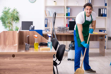 Photo for Young handsome contractor cleaning the office - Royalty Free Image