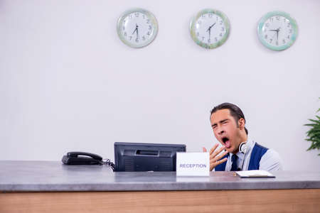 Photo for Young man receptionist at the hotel counter - Royalty Free Image
