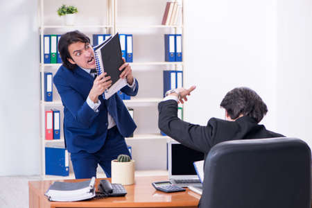 Photo pour Boss and his male assistant working in the office - image libre de droit