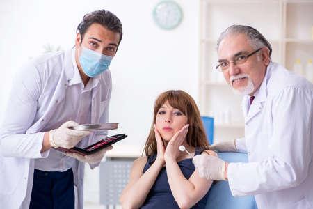 Photo pour Two male doctors and young woman in plastic surgery concept - image libre de droit