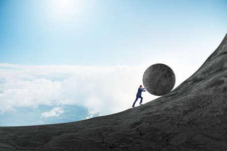 Foto de Man pushing large stone to the top - Imagen libre de derechos
