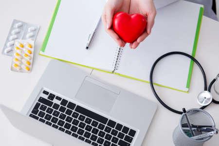 Photo pour Doctor checking up heart in medical concept - image libre de droit