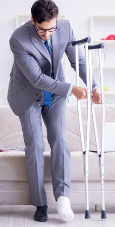 Photo pour Businessman with crutches and broken leg at home working - image libre de droit