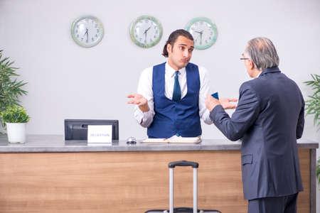 Photo pour Old businessman at the hotel reception - image libre de droit