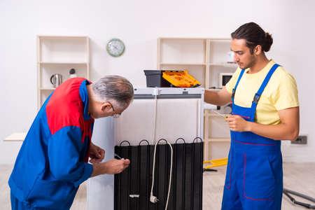 Photo pour Two contractors repairing fridge at workshop - image libre de droit