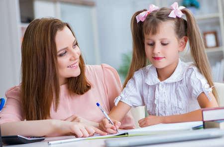 Foto de Mother helping her daughter to do homework - Imagen libre de derechos