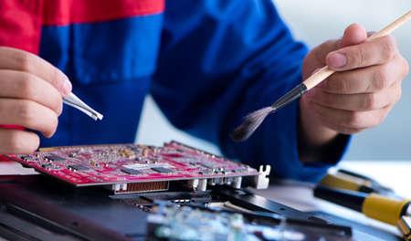 Photo pour Repairman working in technical support fixing computer laptop tr - image libre de droit