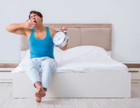 Photo pour Young man waking up in bed - image libre de droit