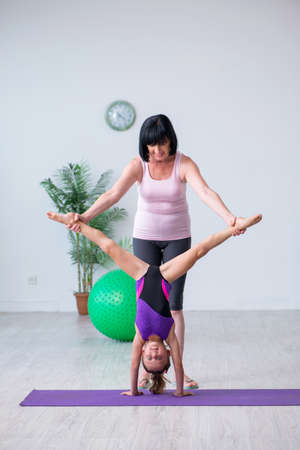 Photo pour Girl and mother exercising at home - image libre de droit