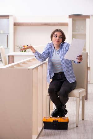 Photo pour Young beautiful woman assembling furniture at home - image libre de droit