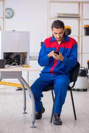 Photo pour Young male contractor repairing refrigerator at workshop - image libre de droit