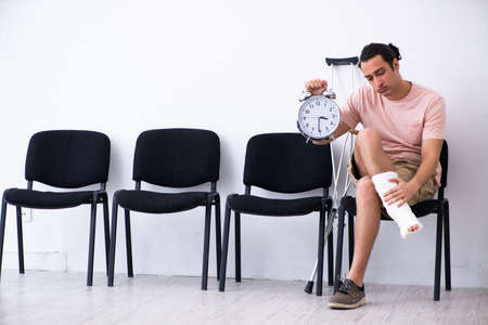 Photo pour Young injured man waiting for his turn in hospital hall - image libre de droit