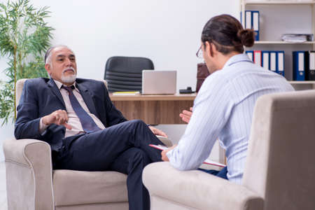 Photo pour Old man visiting young male doctor psychologist - image libre de droit
