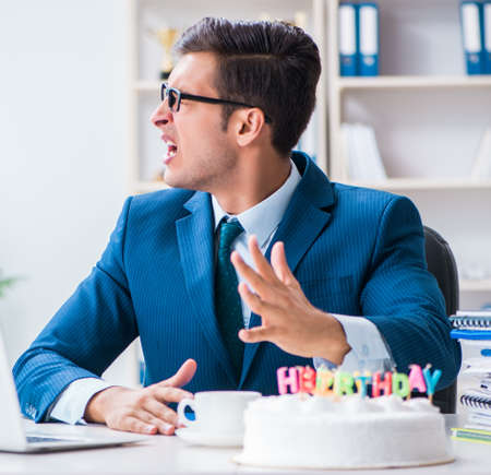Photo for Young businessman celebrating birthday alone in office - Royalty Free Image