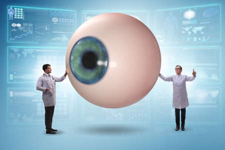 Foto de Doctor examining giant eye in medical concept - Imagen libre de derechos
