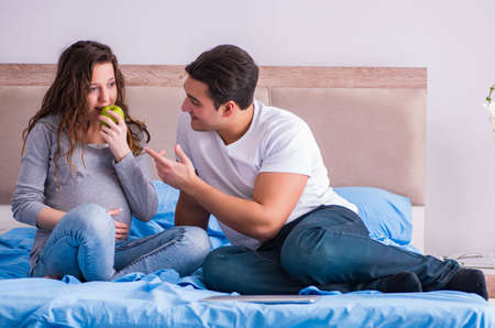 Photo pour Young family with pregnant wife expecting baby in bed - image libre de droit