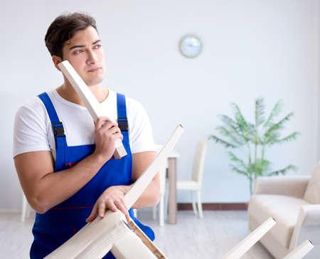 Photo pour Man repairing chair in the room - image libre de droit