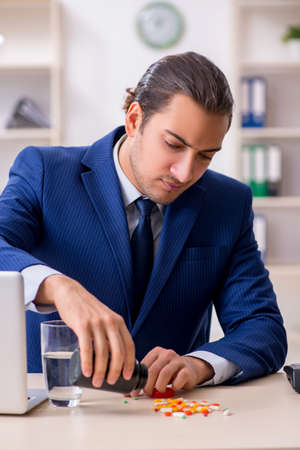 Photo pour Young male employee and a lot of pills on the desk - image libre de droit