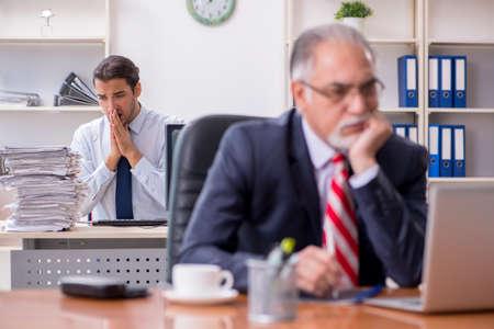 Foto de Old boss and young male employee in the office - Imagen libre de derechos