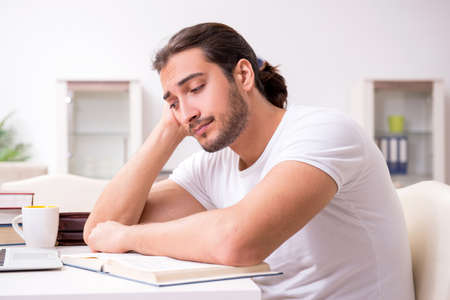 Photo pour Young male student preparing for exams at home - image libre de droit