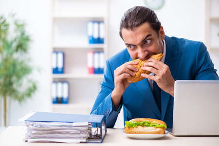 Photo for Young male employee having breakfast at workplace - Royalty Free Image
