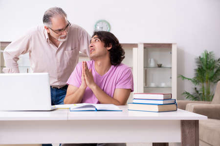 Photo for Old father helping his son in exam preparation - Royalty Free Image