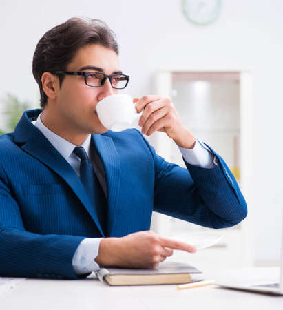 Photo pour Young handsome businessman drinking coffee in the office - image libre de droit
