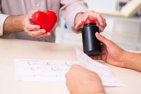Photo pour Old man visiting young male doctor cardiologist - image libre de droit