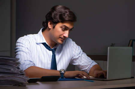 Photo for Young financial manager working late at night in office - Royalty Free Image