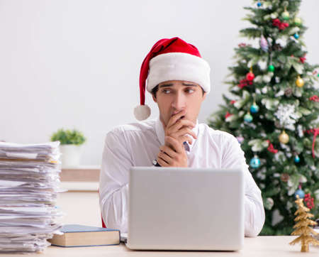 Photo for Young worker working in office on christmas shift - Royalty Free Image