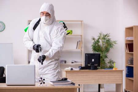 Foto de Contractor disinfecting office for COVID-19 coronavirus - Imagen libre de derechos