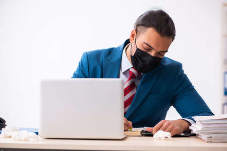 Photo pour Sick male employee suffering at workplace from coronavirus - image libre de droit