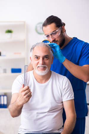 Photo pour Old man visiting young male doctor in hair transplantation conce - image libre de droit