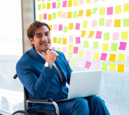 Foto de Young handsome man in wheelchair with many conflicting prioritie - Imagen libre de derechos