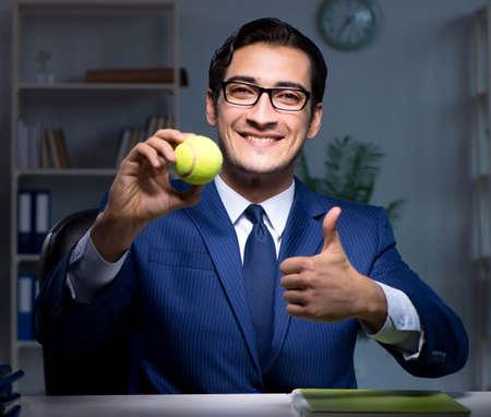 Foto de Young employee with tennis ball - Imagen libre de derechos