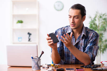Photo pour Young male technician repairing mobile phone - image libre de droit