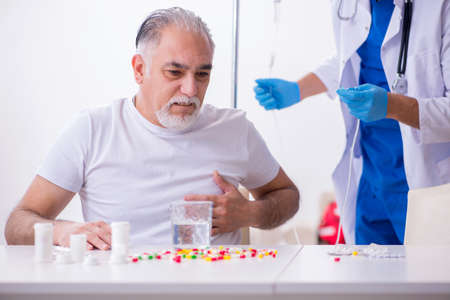 Photo pour Young male doctor visiting old male patient at home - image libre de droit