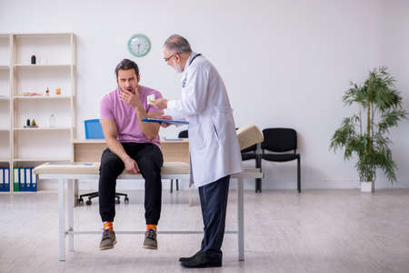 Photo for Young male patient visiting old male doctor - Royalty Free Image