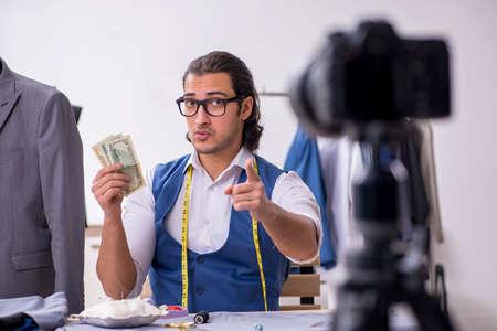 Photo pour Young male tailor recording video for his blog - image libre de droit