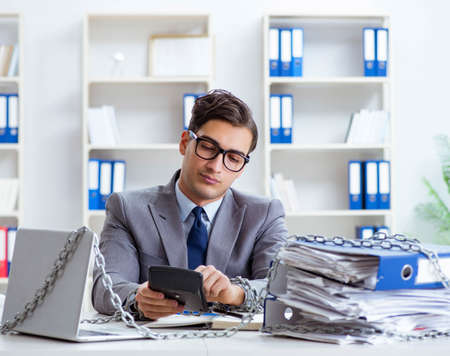 Photo for Busy employee chained to his office desk - Royalty Free Image