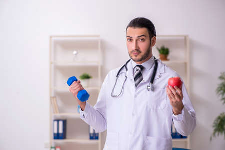 Photo pour Young male doctor working in the clinic - image libre de droit