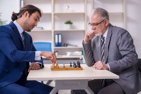 Photo pour Two businessmen playing chess in the office - image libre de droit