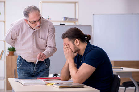 Photo pour Old teacher and young male student in the classroom - image libre de droit